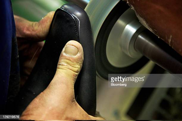 An employee uses a machine to work a completed upper before attaching a sole during the manufacture of an Oliver Sweeney brand shoe at a factory in...