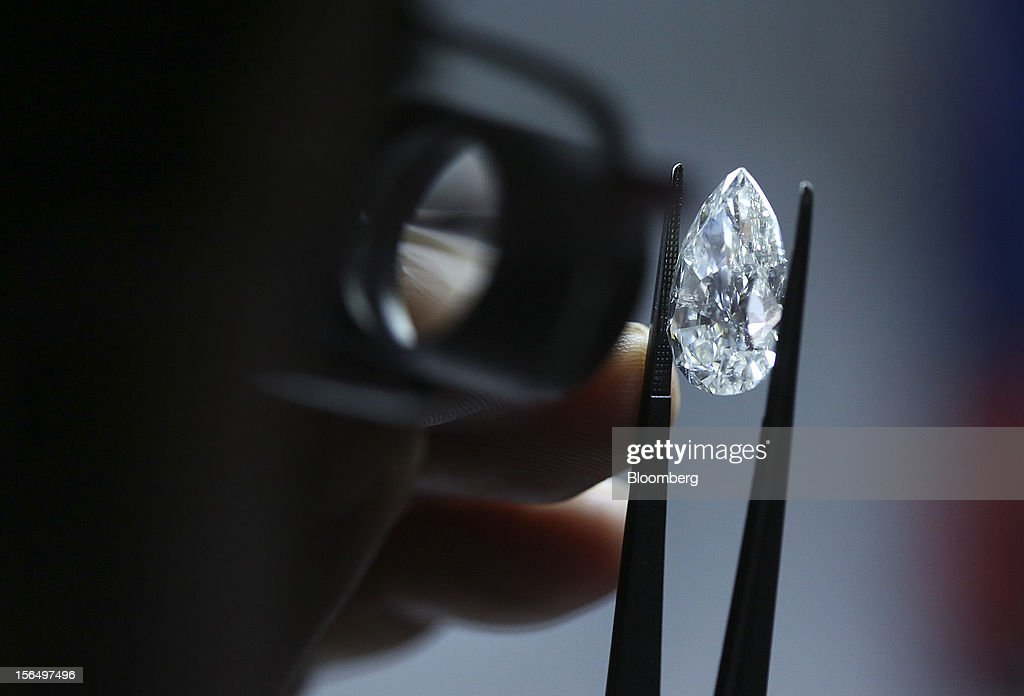 An employee uses a magnifier to inspect a finished pear-shaped diamond before final classification at the Shrenuj Botswana Ltd. sightholder office in Gaborone, Botswana, on Thursday, Oct. 25, 2012. De Beers, the biggest diamond producer by revenue, is moving the sorting and trading of rough stones to Botswana from London to secure access to the world's largest supplier of diamonds by value and challenge Antwerp's dominance as the world's biggest trading hub for rough diamonds. Photographer: Chris Ratcliffe/Bloomberg via Getty Images