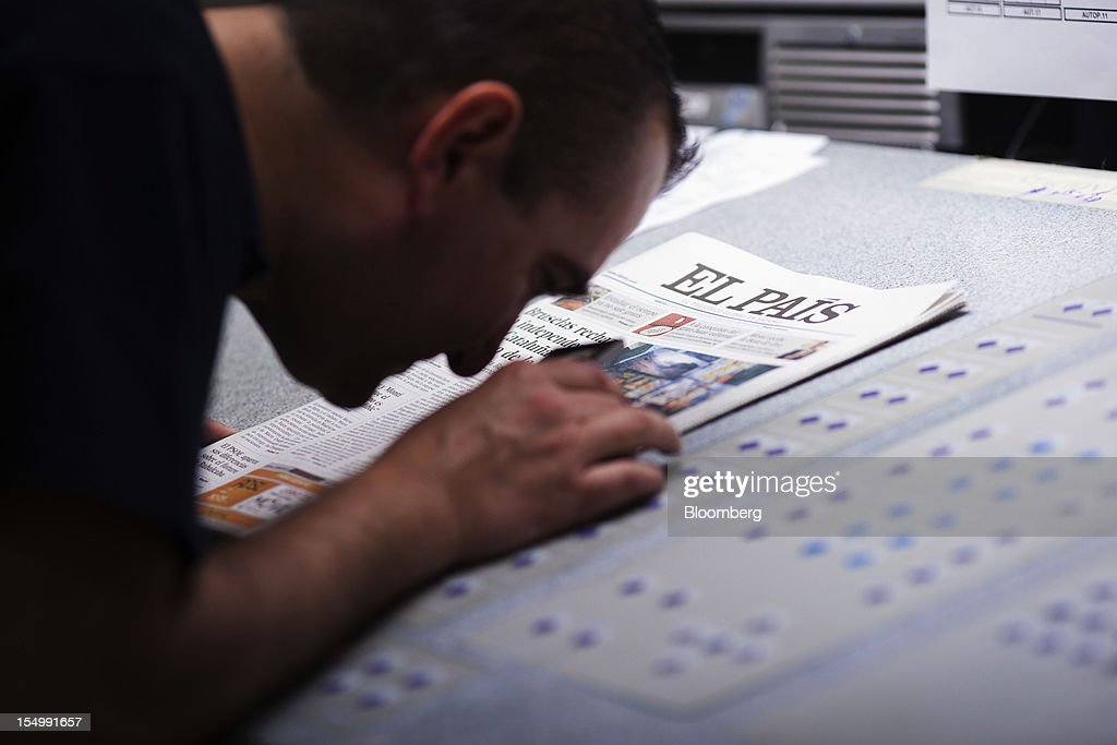 An employee uses a magnifying glass to check the print quality of an El Pais daily newspaper during printing at the El Pais printing plant in Madrid, Spain, on Tuesday, Oct. 30, 2012. Prisa, the publisher of El Pais newspaper, has announced staff reductions and salary cuts. Photographer: Angel Navarrete/Bloomberg via Getty Images