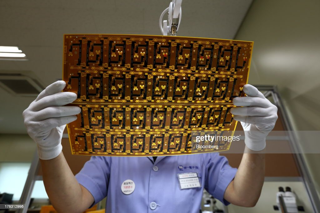 An employee uses a magnifying glass to inspect a Flexible Printed Circuit Board (F-PCB) panel on the production line at the Seil Electronics Co. factory in Incheon, South Korea, on Wednesday, Aug. 28, 2013. South Korea has surpassed Brazil, Russia and India to become the second-biggest emerging stock market for the first time since 2006, as a stable won and record current-account surplus lure investors. Photographer: SeongJoon Cho/Bloomberg via Getty Images