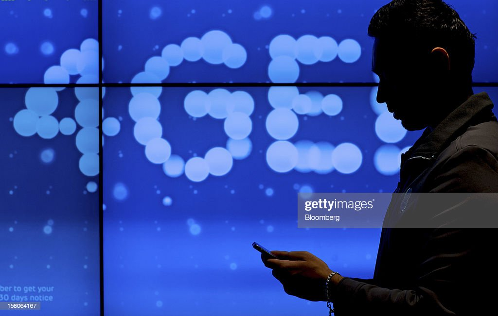 An employee uses a mobile phone displayed in front of a giant screen advertising EE's (Everything Everywhere) 4G network, a joint venture between France Telecom SA and Deutsche Telekom AG, inside the company's store in Stratford, U.K., on Monday, Dec. 5, 2012. France Telecom CEO Stephane Richard said in an interview last month that the Paris-based company has received interest from private-equity firms seeking a minority stake in the 50-50 venture, and may also consider an initial public offering of the unit. Photographer: Jason Alden/Bloomberg via Getty Images