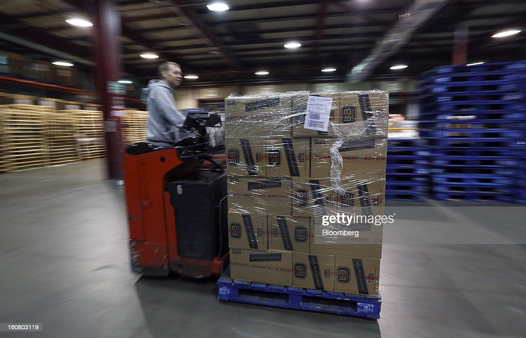 An employee uses a pallet truck to move shrink-wrapped boxes of Lambert and Butler cigarettes, marked for 'Export', inside a warehouse at Imperial Tobacco Group Plc's factory in Nottingham, U.K., on Friday, Feb. 1, 2013. Imperial Tobacco Group Plc is Europe's second-biggest tobacco company and generates about 40 percent of its profit from the region. Photographer: Chris Ratcliffe/Bloomberg via Getty Images