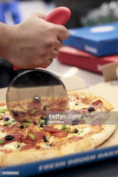 An employee uses a pizza cutter to slice a freshly cooked pizza ahead of delivery inside a Domino's Pizza Group Plc store in Hanwell London UK on...