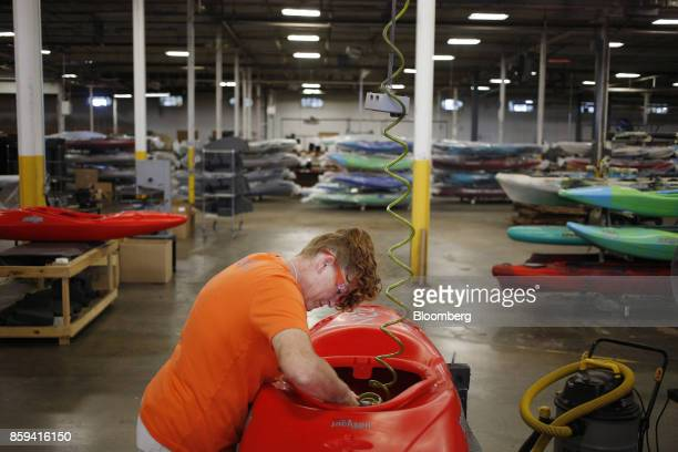 An employee uses a power tool during production of a plastic kayak at the Jackson Kayak Inc factory in Sparta Tennessee US on Wednesday Oct 4 2017...
