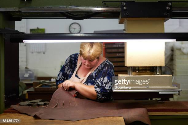 An employee uses a press to cut leather for ball gloves at the Nokona manufacturing facility in Nocona Texas US on Thursday July 27 2017 Since the...