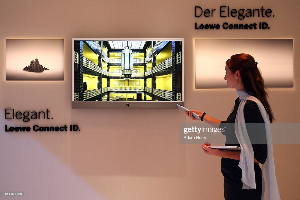An employee uses a remote control with a Loewe Connect ID television on display at the Internationale Funkausstellung (IFA) 2012 consumer electronics trade fair on September 1, 2012 in Berlin, Germany. IFA 2012 is open to the public from today until September 5.