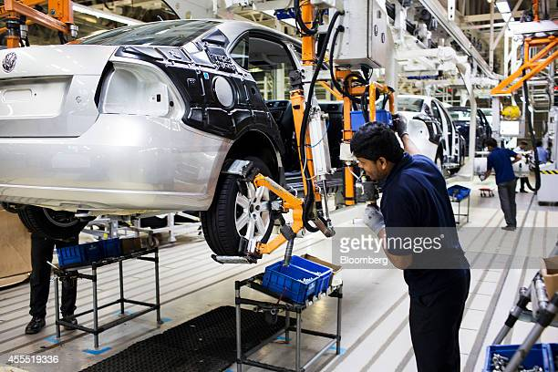 An employee uses a robotic arm to fit a wheel onto a Volkswagen AG Vento automobile on the production line at the Volkswagen India Pvt plant in...