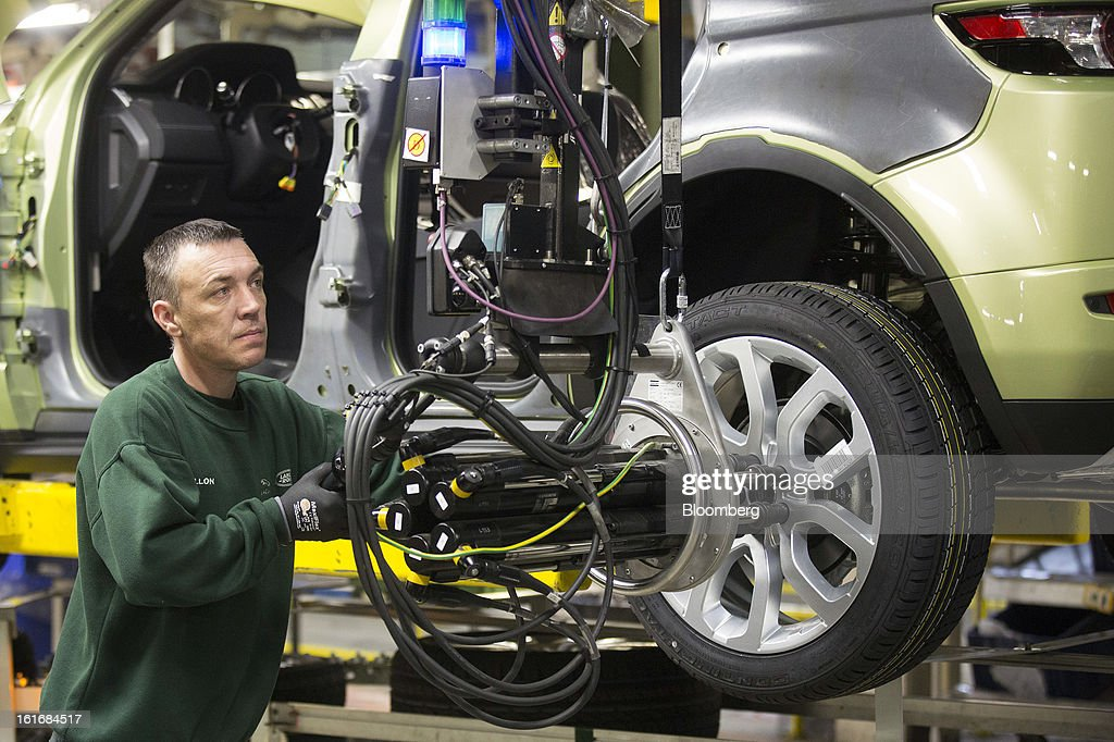 An employee uses a robotic arm to fix an alloy wheel to the hub of a Range Rover Evoque SUV automobile, produced by Jaguar Land Rover Plc, a unit of Tata Motors Ltd., as it travels along the production line at the company's assembly plant in Halewood, U.K., on Wednesday, Feb. 13, 2013. Carmakers from Ford Motor Co. to Audi AG and Jaguar Land Rover Plc are using record amounts of aluminium to replace heavier steel, providing relief to producers of the metal confronting excess supplies and depressed prices. Photographer: Simon Dawson/Bloomberg via Getty Images