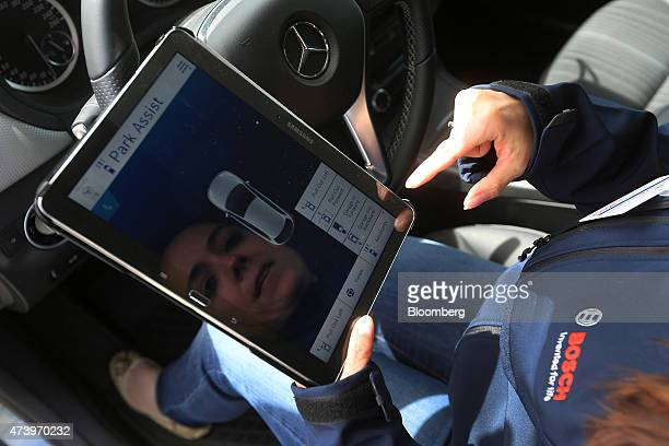An employee uses a Samsung Electronics Co tablet device during a remote control automobile parking demonstration at the Robert Bosch GmbH driverless...