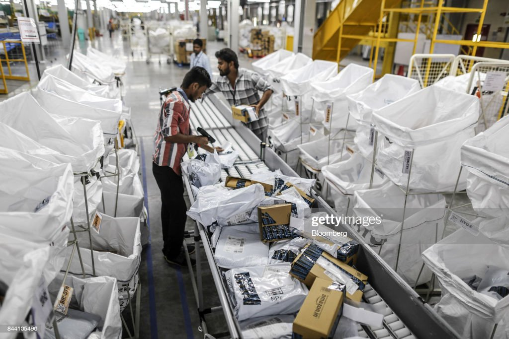 An employee uses a scanner as he prepares a package for shipment at the Amazon.com Inc fulfillment center in Hyderabad, India on Thursday, Sept. 7, 2017. Amazon opened its largest Indian fulfillment center in Hyderabad. The center spans 400,000 square feet with 2.1m cubic feet of storage capacity the company said in a statement. Photographer: Dhiraj Singh/Bloomberg via Getty Images