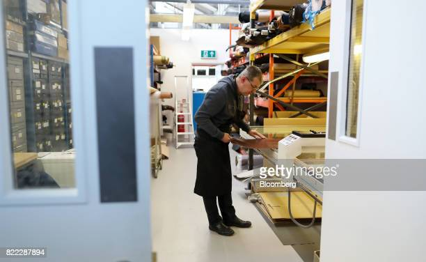 An employee uses a scanning machine to measure a section of hide at the Alfred Dunhill Ltd London Leather Workshop in London UK on Tuesday July 25...