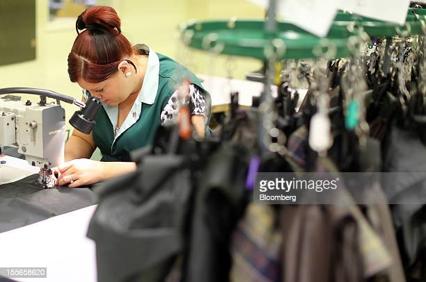 An employee uses a sewing machine to stitch material on the production line at J Barbour Sons Ltd in South Shields UK on Tuesday Nov 6 2012 While the...