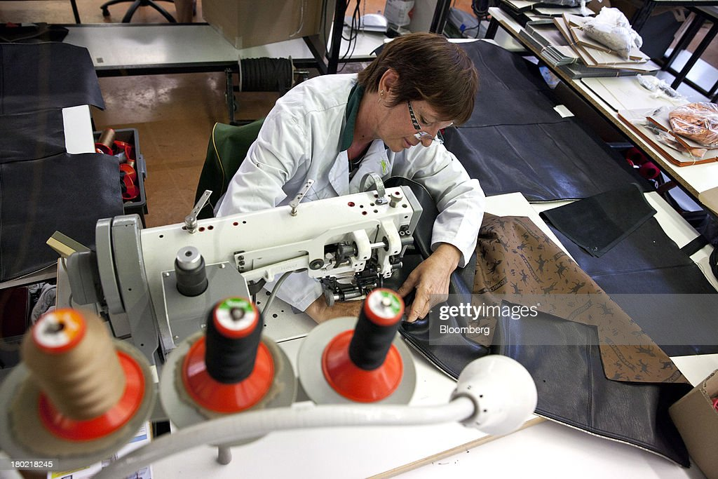 An employee uses a sewing machine to work on the lining for a Le Pliage Cuir bag during the production process at the Longchamp SAS workshop in Segre, France, on Monday, Sept. 9, 2013. Longchamp SAS, the French handbag maker, which is known for foldable Le Pliage nylon tote bags, expects sales in China to rise, Chief Executive Officer Jean Cassegrain said. Photographer: Balint Porneczi/Bloomberg via Getty Images
