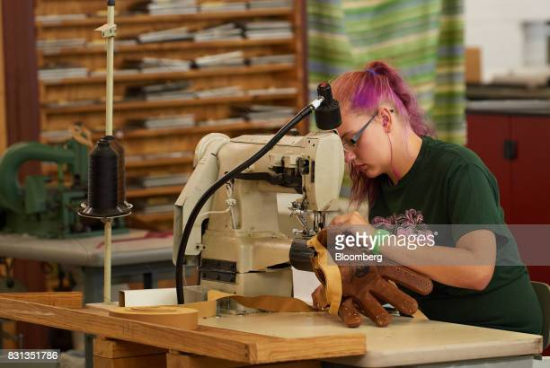 An employee uses a sewing machine while assembling a ball glove at the Nokona manufacturing facility in Nocona Texas US on Thursday July 27 2017...