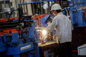 An employee uses a shear welding machine on the production line of the tube mill at the manufacturing facility of Uttam Galva Steels Ltd the Indian...