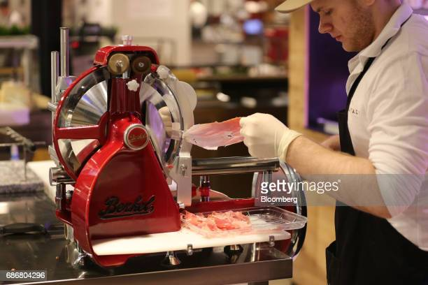 An employee uses a slicing machine to cut thin slices of Italian cured meat inside the new Eataly food store operated by Eataly Net Srl at the...