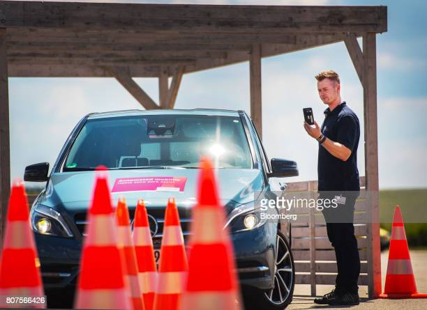 An employee uses a smartphone remote park assist system app to maneuver a MercedesBenz BClass luxury automobile during the Robert Bosch GmbH mobility...
