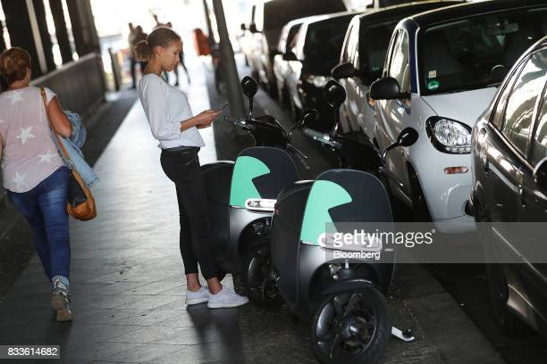 An employee uses a smartphone to book a Coup eScooter electric hire vehicle operated by Robert Bosch GmbH in Berlin Germany on Thursday Aug 17 2017...