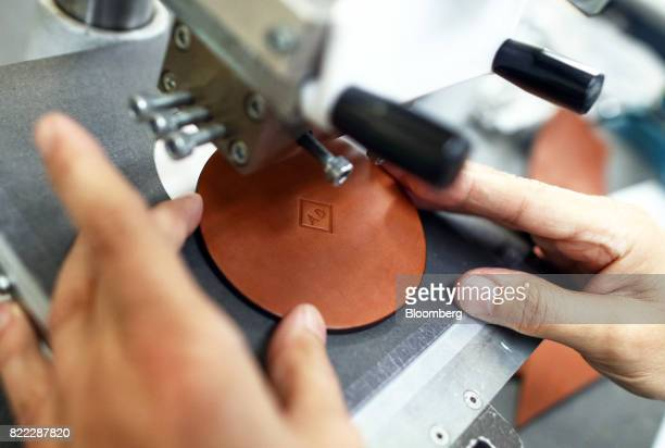 An employee uses a stamping machine to emboss the initials 'AD' on to a section of leather at the Alfred Dunhill Ltd London Leather Workshop in...