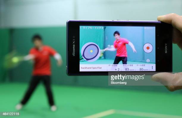 An employee uses a tennis racket fitted with Sony Corp's Smart Tennis Sensor device as a Sony smartphone displays an app tracking the data collected...