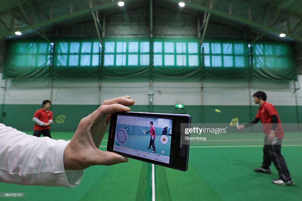 An employee uses a tennis racket fitted with Sony Corp.'s Smart Tennis Sensor device as a Sony smartphone displays an app tracking the data collected by the sensor during a demonstration in Tokyo, Japan, on Monday, Jan. 20, 2014. The development of wearable technology such as eyeglasses, watches and earpieces is expanding as consumers seek new ways to integrate computers into everyday life. Photographer: Yuriko Nakao/Bloomberg via Getty Images