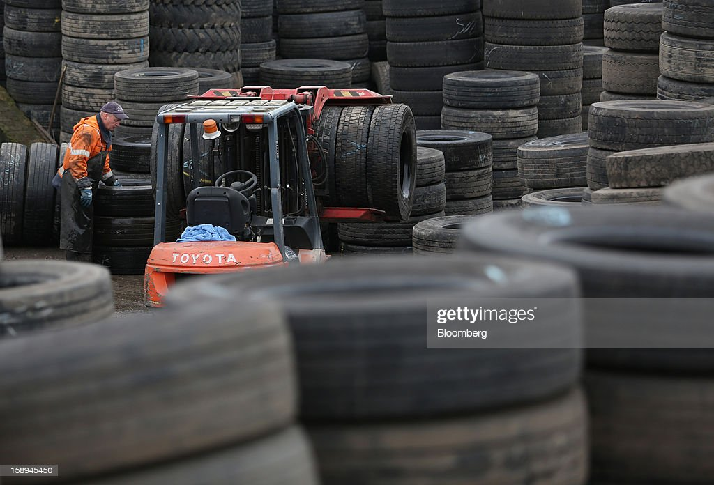 An employee uses a Toyota Motor Co. forklift truck to arrange used vehicle tires for storage in the yard of the UK Tyre Co. in London, U.K., on Thursday, Jan. 3 2013. Rubber surged to an eight-month high on the first trading day of 2013. Photographer: Chris Ratcliffe/Bloomberg via Getty Images