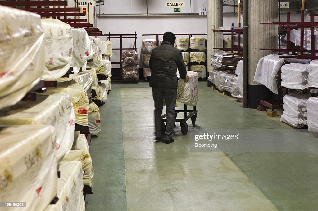 An employee uses a trolley to wheel a new coffin into place in the warehouse of the Empresa Mixta de Servicios Funerarios de Madrid SA funeral parlour in Madrid, Spain, on Monday, Dec. 17, 2012. Spain, responding to street protests and reports of suicides linked to foreclosures, introduced rules to help protect families from eviction, increasing the risk of creditor losses and weakening an already fragile banking system. Photographer: Angel Navarrete/Bloomberg via Getty Images