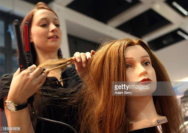An employee uses a Valera hair crimping iron on a mannequin head at the Internationale Funkausstellung 2012 consumer electronics trade fair on August...