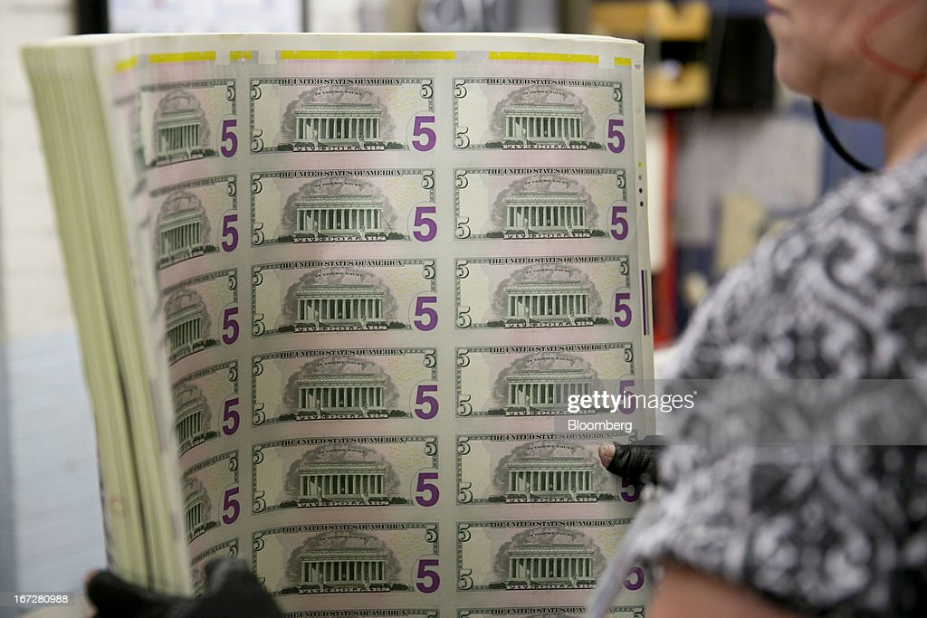 An employee uses a vibrating table to loosen stacks of five dollar notes before being cut into singles at the Bureau of Engraving and Printing in...