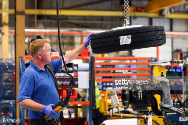 An employee uses a winch to move a wheel on the bus assembly line at the Alexander Dennis Ltd factory in Guildford UK on Monday Sept 11 2017...