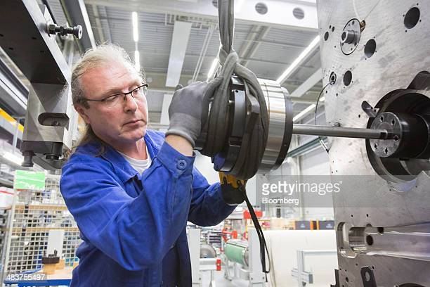 An employee uses a winch to position a component on a Heidelberg industrial printing press in the Heidelberger Druckmaschinen AG manufacturing hall...