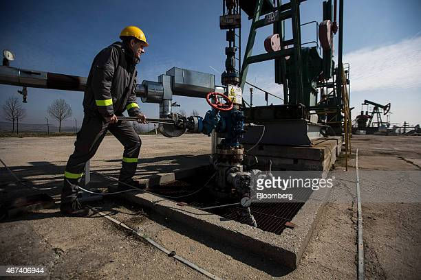 An employee uses a wrench to adjust a valve on oil pumping gear also known as nodding donkeys or pump jacks at an oil plant operated by MND AS in...