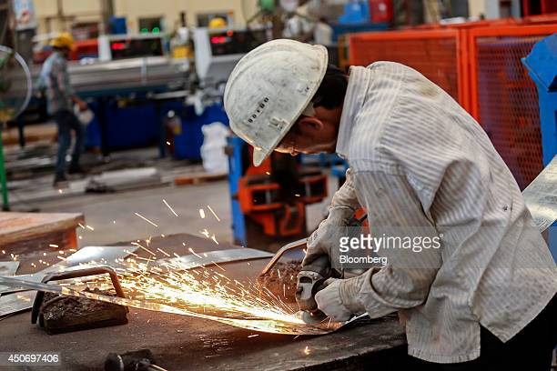 An employee uses an angle grinder on the production line of the tube mill at the manufacturing facility of Uttam Galva Steels Ltd the Indian unit of...