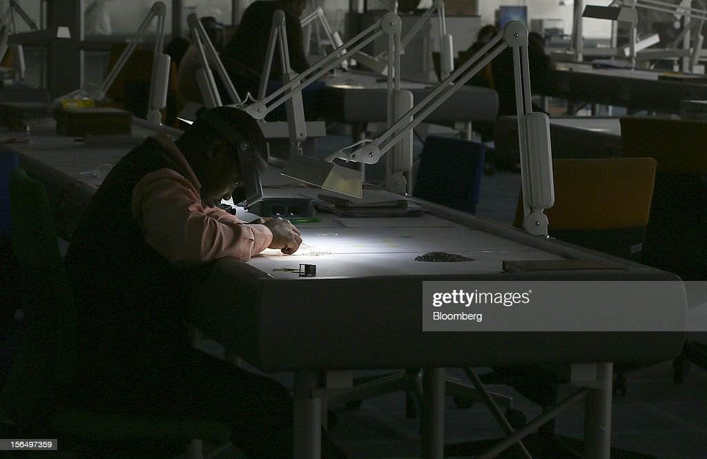 An employee uses an angled light and a magnifier to illuminate uncut diamonds at a sorting table in DTC Botswana, a unit of De Beers, in Gaborone, Botswana, on Thursday, Oct. 25, 2012. De Beers, the biggest diamond producer by revenue, is moving the sorting and trading of rough stones to Botswana from London to secure access to the world's largest supplier of diamonds by value and challenge Antwerp's dominance as the world's biggest trading hub for rough diamonds. Photographer: Chris Ratcliffe/Bloomberg via Getty Images