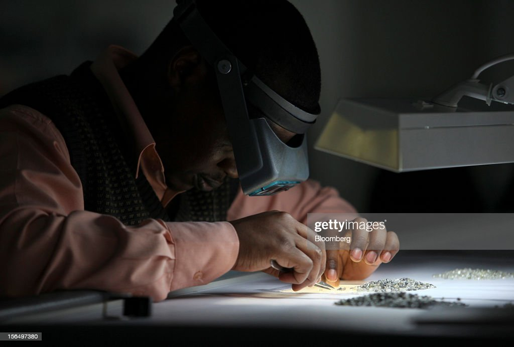 An employee uses an angled light and a magnifier to sort uncut diamonds at a sorting table in DTC Botswana, a unit of De Beers, in Gaborone, Botswana, on Thursday, Oct. 25, 2012. De Beers, the biggest diamond producer by revenue, is moving the sorting and trading of rough stones to Botswana from London to secure access to the world's largest supplier of diamonds by value and challenge Antwerp's dominance as the world's biggest trading hub for rough diamonds. Photographer: Chris Ratcliffe/Bloomberg via Getty Images