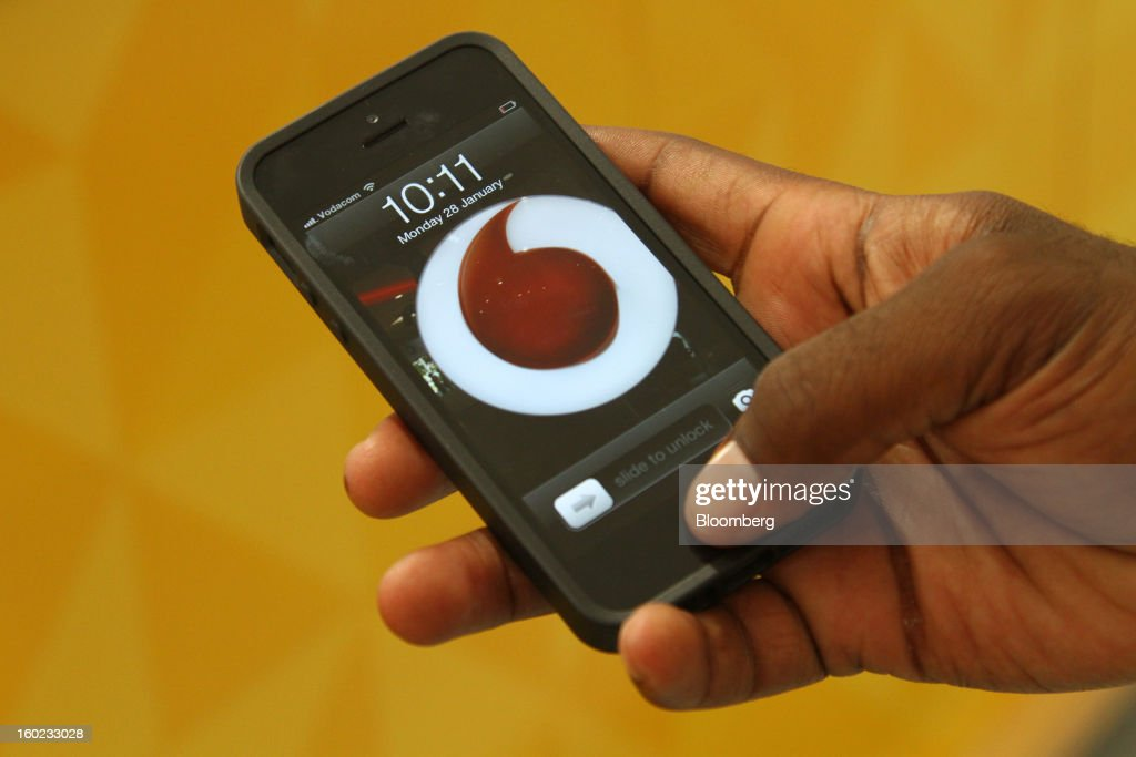 An employee uses an Apple Inc. iPhone displaying a Vodafone logo on its homescreen inside a store at Vodaworld, the headquarters of Vodacom Group Ltd., Vodafone's biggest African business, in Johannesburg, South Africa, on Monday, January 28, 2013. Almost two decades after Vodafone Group Plc entered Africa, the region -- where most people earn less than $2 a day and mobile phone towers run on diesel -- is turning into one of the company's biggest profit generators. Photographer: Nadine Hutton/Bloomberg via Getty Images