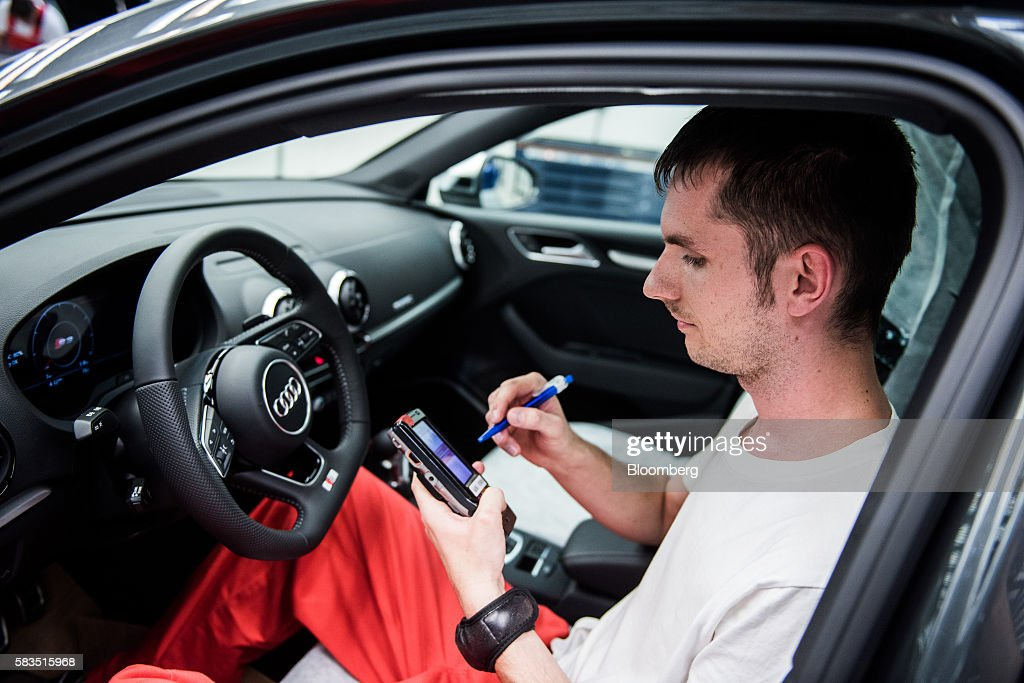 An employee uses an electronic handheld device as he performs a quality control check on the interior of an Audi automobile inside the Audi AG...