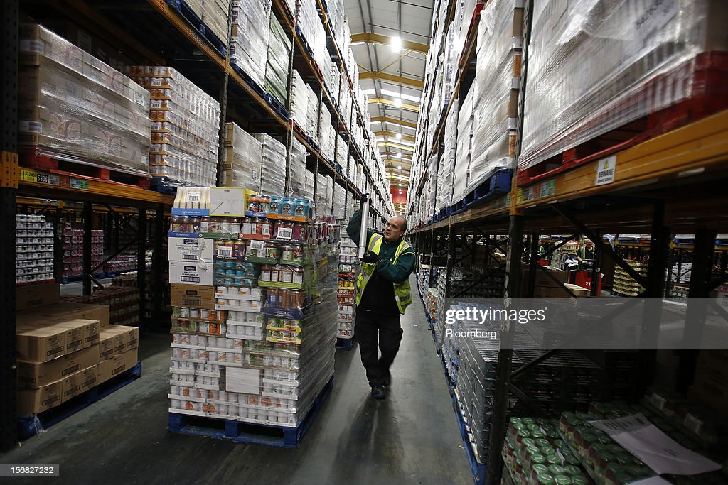 An employee uses cellophane to wrap a pallet loaded with produce ahead of transporting to stores inside WM Morrison Supermarkets Plc's distribution center in Wakefield, U.K., on Thursday, Nov. 22, 2012. Britain's economy will return to growth next year after stagnating in 2012, with expansion weighted in the second half, according to Bank of England projections published yesterday. Photographer: Simon Dawson/Bloomberg via Getty Images