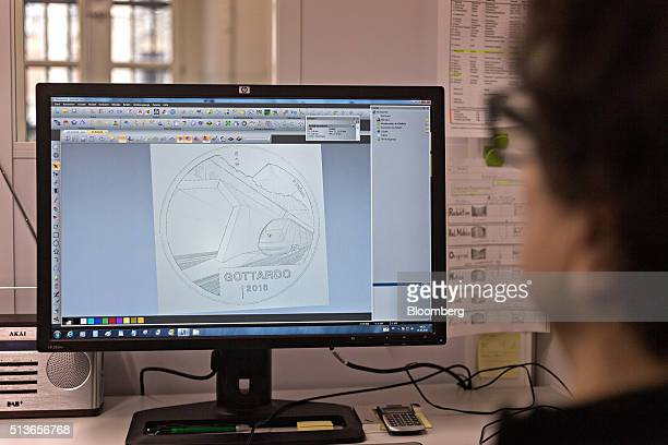 An employee uses computeraided design and computeraided manufacturing software to work on the design of the Gothard Tunnel commemorative twenty Swiss...
