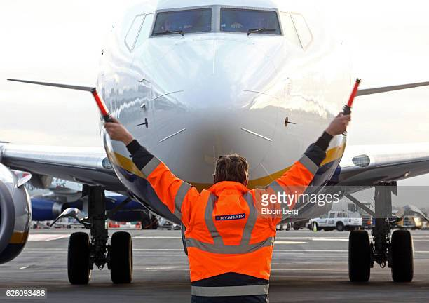 An employee uses glow sticks to guide a Ryanair Holdings Plc aircraft into position at Dublin Airport operated by Dublin Airport Authority in Dublin...