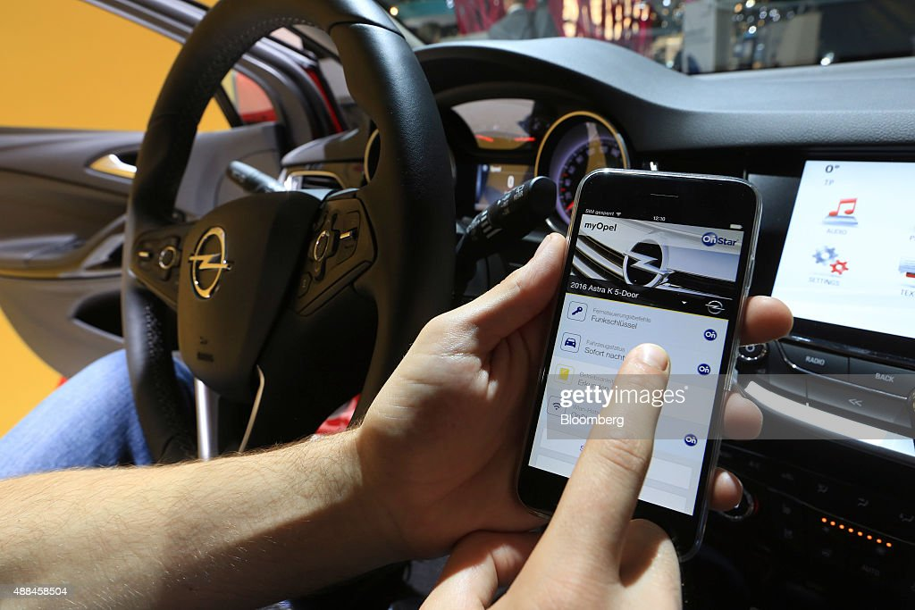 An employee uses the OnStar smartphone app Adam Opel AG's incar connected technology inside an Opel Astra automobile at the IAA Frankfurt Motor Show...