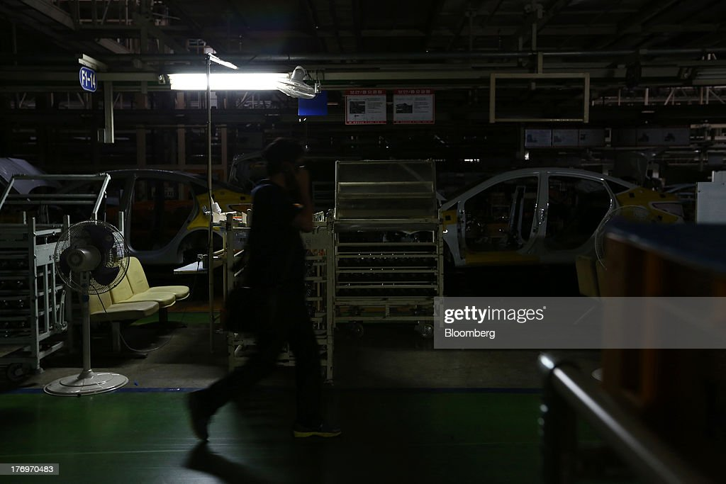 An employee using a mobile phone walks past the halted assembly line at the Hyundai Motor Co. plant during a strike by the company's labor union in Ulsan, South Korea, on Tuesday, Aug. 20, 2013. Union members at Hyundai Motor, South Korea's largest automaker, staged a partial strike today that will continue tomorrow as they demand higher wages amid increasing competition with Japanese carmakers. Photographer: SeongJoon Cho/Bloomberg via Getty Images