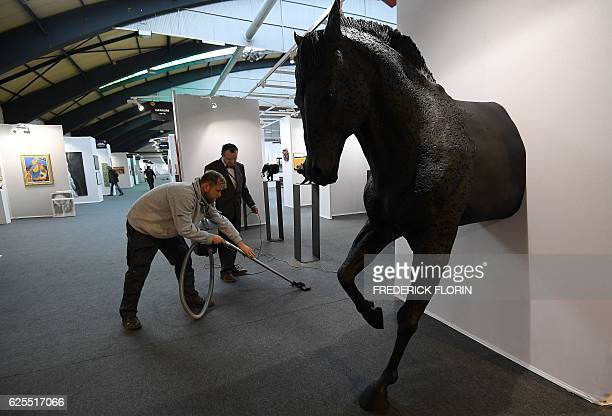 An employee vacuumcleans near a sculpture by French artist Olivier Courty during a private preview of the 'START' European contemporary art fair on...