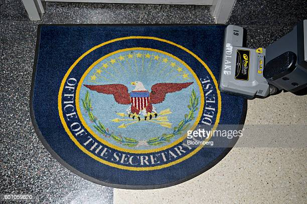 An employee vacuums a rug outside the office of Chris Lynch director of the US Defense Department's Defense Digital Service at the Pentagon in...