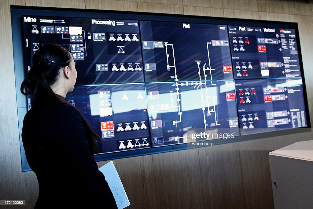 An employee views a monitor tracking the real-time flow of iron ore from pit-to-port at BHP Billiton Ltd.'s new Integrated Remote Operations Center in Perth, Australia, on Tuesday, July 2, 2013. BHP Billiton is the world's largest mining company. Photographer: Sergio Dionisio/Bloomberg via Getty Images