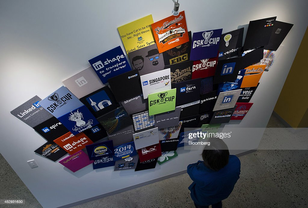 An employee views a wall display of t-shirts at LinkedIn Corp. headquarters in Mountain View, California, U.S., on Monday, July 28, 2014. LinkedIn Corp. is scheduled to release earnings figures on July 31. Photographer: David Paul Morris/Bloomberg via Getty Images