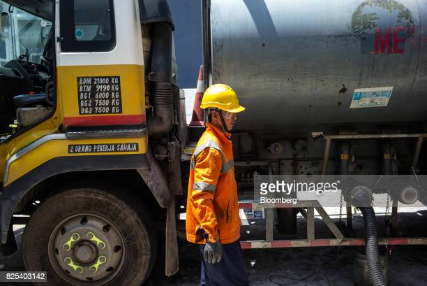An employee waits as fuel from a tanker truck is transferred to gas fuel tanks at a Royal Dutch Shell Plc gas station in Kota Kinabalu in Sabah...