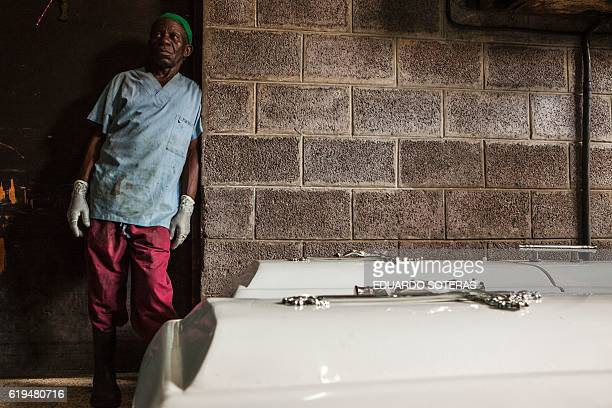 An employee waits next to empty coffins at the Bondeko morgue in Kinshasa on October 31 2016 The bodies of six militants of the Congolese opposition...