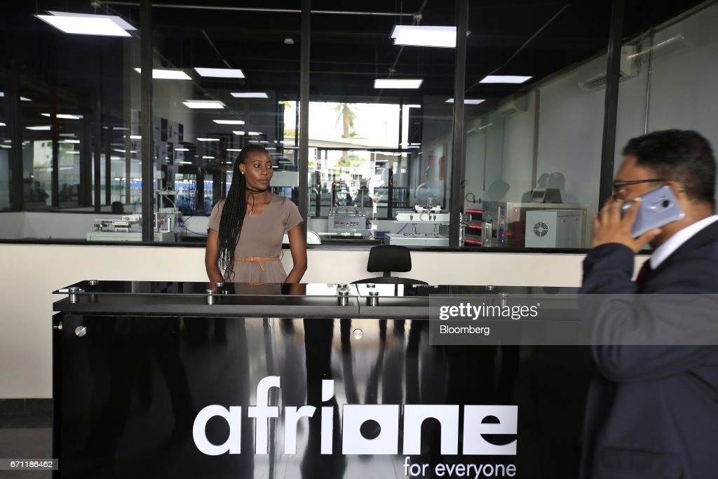 An employee waits to greet visitors during a launch event for the AfriOne Gravity Z1 smartphone at the new AfriOne Ltd. manufacturing plant in Lagos, Nigeria, on Friday, April 21, 2017. The plant has the capacity to produce some 120,000 units per month. Photographer: George Osodi/Bloomberg via Getty Images