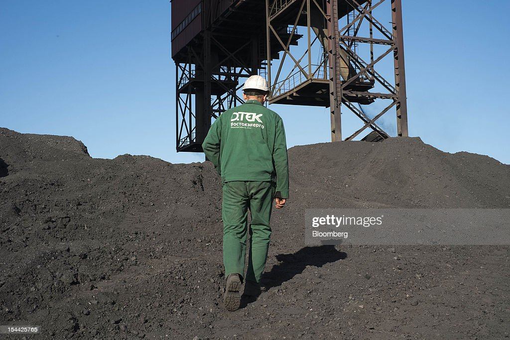 An employee walks across a coal storage area at the Vostok Energo power plant, operated by the Donbass Fuel & Energy Co., or DTEK, in Donetsk, Ukraine, on Thursday, Oct. 18, 2012. DTEK, Ukraine's largest private coal and energy producer, signed a supply contract with OAO OGK-2, the Russian wholesale power generator controlled by OAO Gazprom. Photographer: Vincent Mundy/Bloomberg via Getty Images